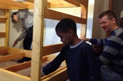 The boys help the team assemble the beds.