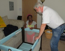 One of Bethel's delivery team members sets up the pack-n-play with mom.